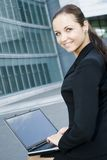 Businesswoman using laptop outside office stock image