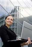 Businesswoman using laptop outside office. Young businesswoman using laptop outside office Stock Photo