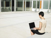 Businesswoman Using Laptop Outside Office Royalty Free Stock Photography