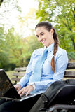 Businesswoman using laptop in park Stock Images