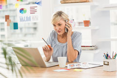 Businesswoman using laptop while on the phone Royalty Free Stock Photos