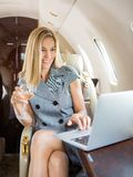 Businesswoman Using Laptop In Private Jet. Happy businesswoman holding wineglass while using laptop in private jet royalty free stock photography