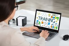 Businesswoman Using Laptop Showing Training Concept. Close-up Of A Businesswoman Using Laptop Showing Training Concept At White Desk Royalty Free Stock Images