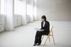 Businesswoman Using Laptop While Sitting On Chair In Warehouse Royalty Free Stock Photo
