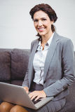Businesswoman using laptop while sitting on sofa Royalty Free Stock Photos