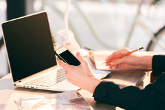 Businesswoman using laptop and smartphone with blank screens Royalty Free Stock Photography