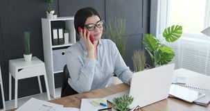 Businesswoman using laptop and talking on mobile phone stock footage