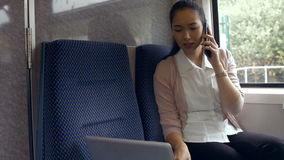 Businesswoman using laptop on the train stock footage