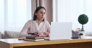 Businesswoman using laptop for video conferencing. Young businesswoman discussing on video conference using laptop at office stock video footage