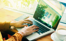 Businesswoman using laptop on wooden table in coffee shop with a Royalty Free Stock Photos