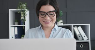 Businesswoman using laptop at workplace. Smiling businesswoman using laptop at office stock video
