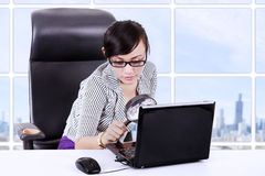 Businesswoman using magnifying glass on laptop Stock Photo