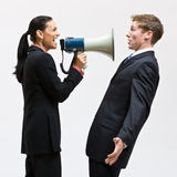 Businesswoman using megaphone. Businesswoman using a megaphone on a co-worker Stock Photos