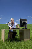 Businesswoman Using Megaphone In A Green Field Stock Image