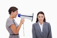 Businesswoman using megaphone to yell at colleague Stock Image