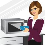 Businesswoman using microwave to heat homemade food Stock Images