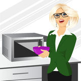 Businesswoman using microwave to heat homemade food. Attractive businesswoman using microwave to heat homemade food on business office kitchen Stock Photos