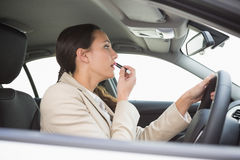 Businesswoman using mirror to put on lipstick while driving Royalty Free Stock Photos