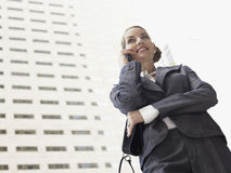 Businesswoman Using Mobile Phone Against Tall Office Building Royalty Free Stock Photos