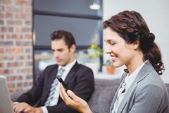 Businesswoman using mobile phone while colleague working Royalty Free Stock Photography