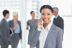 Businesswoman using mobile phone with colleagues behind Royalty Free Stock Photos