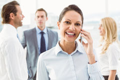 Businesswoman using mobile phone with colleagues behind Royalty Free Stock Images