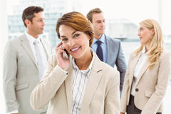 Businesswoman using mobile phone with colleagues behind Stock Images