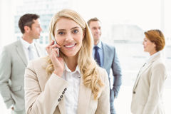 Businesswoman using mobile phone with colleagues behind Stock Photos
