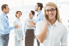 Businesswoman using mobile phone with colleagues behind Stock Photography