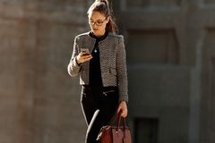 Businesswoman using mobile phone while commuting to office stock image