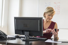 Businesswoman Using Mobile Phone At Computer Desk Royalty Free Stock Images
