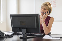 Businesswoman Using Mobile Phone At Computer Desk Royalty Free Stock Image