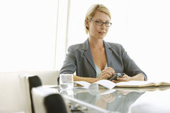Businesswoman Using Mobile Phone At Conference Table Royalty Free Stock Images