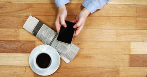 Businesswoman using mobile phone at desk with newspaper and cup of coffee on table. In office stock footage
