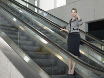 Businesswoman Using Mobile Phone On Escalator Royalty Free Stock Photography