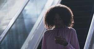 Businesswoman using mobile phone on escalator in a modern office 4k. Front view of African american Businesswoman using mobile phone on escalator in a modern stock video