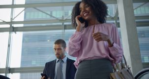 Businesswoman using mobile phone on escalator in a modern office 4k. Low angle view of African American businesswoman using mobile phone on escalator in a modern stock video