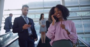 Businesswoman using mobile phone on escalator in a modern office 4k. Low angle view of African American Businesswoman using mobile phone on escalator in a modern stock footage