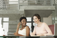 Businesswoman Using Mobile Phone While Female Colleague Writing Royalty Free Stock Images