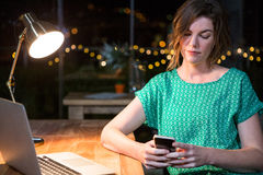 Businesswoman using mobile phone at her desk Royalty Free Stock Photography