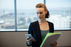 Businesswoman using mobile phone while holding files. Young businesswoman using mobile phone while holding files at office Stock Photo