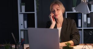 Businesswoman using mobile phone and laptop at night in office. Businesswoman talking on mobile phone and working on laptop late night at office stock video