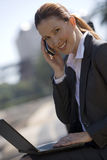 Businesswoman using mobile phone and laptop, outdoors, smiling, side view, portrait (tilt) Royalty Free Stock Photo