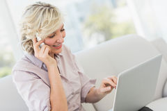 Businesswoman using mobile phone and laptop Royalty Free Stock Image