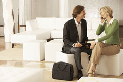 Businesswoman Using Mobile Phone While Looking At Businessman In. Happy businesswoman using mobile phone while looking at businessman in office lobby stock images