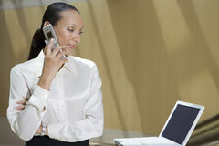 Businesswoman Using Mobile Phone While Looking At Laptop Royalty Free Stock Photography