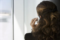 Businesswoman using mobile phone, looking through window, close-up, rear view Royalty Free Stock Photo