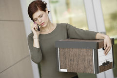 Businesswoman Using Mobile Phone With Moving Box Royalty Free Stock Photography