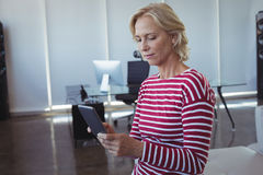 Businesswoman using mobile phone at office Royalty Free Stock Photos
