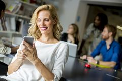 Businesswoman using mobile phone in office Stock Photography